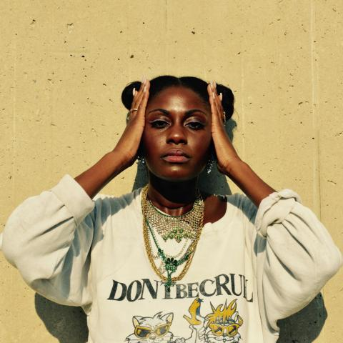 Image of Hip-Hop Artist SAMMUS posed against a tan concrete background