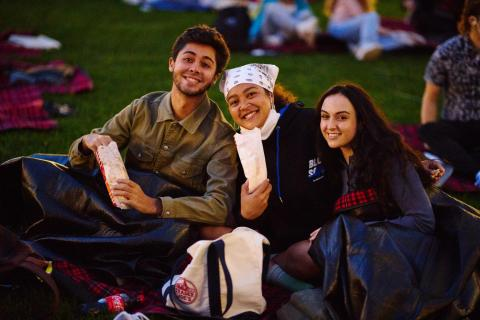 students eating popcorn at the movie on the lawn event
