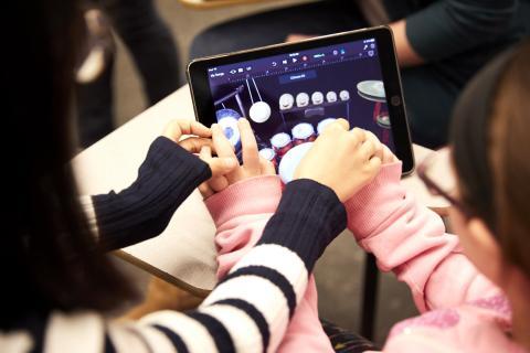 teacher teaching child to use iPad