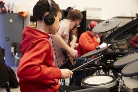 student wearing headphones playing music