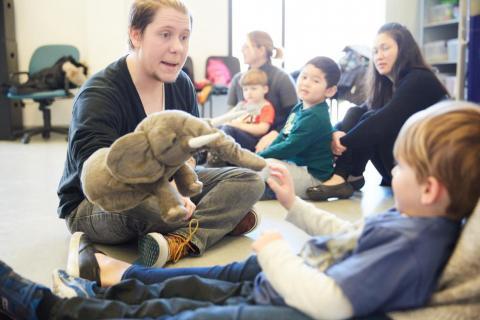 teacher holding elephant puppet for a child