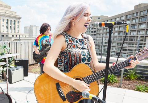 Outdoor performance with a singer-songwriter and a bassist.
