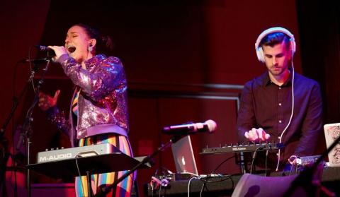 Woman singing and man performing music on a MIDI controller.